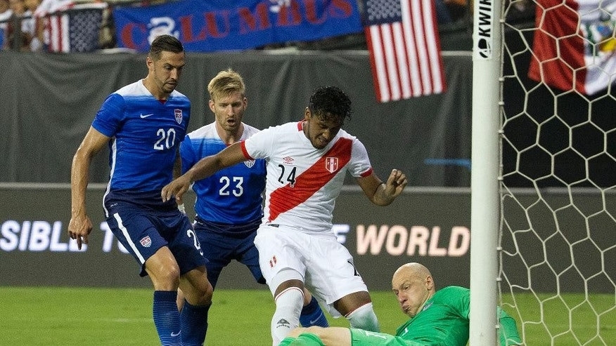 U.S. goalkeeper Brad Guzan blocks a shot made by Peru midfielder Renato Tapia (24) and is helped by his teammates U.S. defenders Geoff Cameron (20), and Tim Ream (23) during the second half of an international friendly soccer match, Friday, Sept. 4, 2015 at RFK Stadium in Washington. (AP Photo/Pablo Martinez Monsivais)