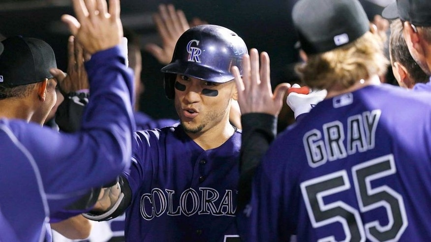 Colorado Rockies' Carlos Gonzalez, center, is congratulated by teammates as he returns to the dugout after hitting a two-run home run off San Francisco Giants relief pitcher George Kontos in the fourth inning of a baseball game, Thursday, Sept.. 3, 2015, in Denver. (AP Photo/David Zalubowski)