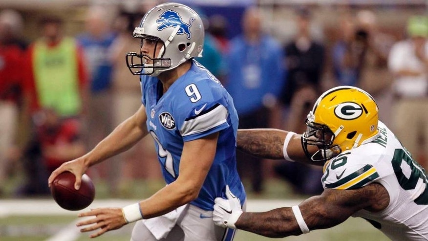 Green Bay Packers outside linebacker Mike Neal (right) reaches in on Detroit Lions quarterback Matthew Stafford during the first half.