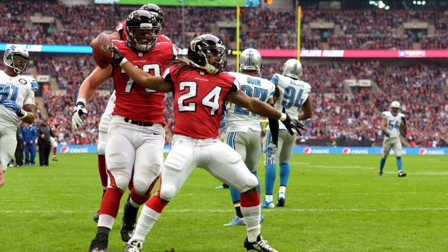 Oct 26, 2014; London, UNITED KINGDOM; Atlanta Falcons running back Devonta Freeman (24) spikes the ball after scoring on a seven-yard touchdown pass in the first quarter against the Detroit Lions as Falcons tackle Ryan Schrader (73) watches in the NFL International Series game at Wembley Stadium. Mandatory Credit: Kirby Lee-USA TODAY Sports