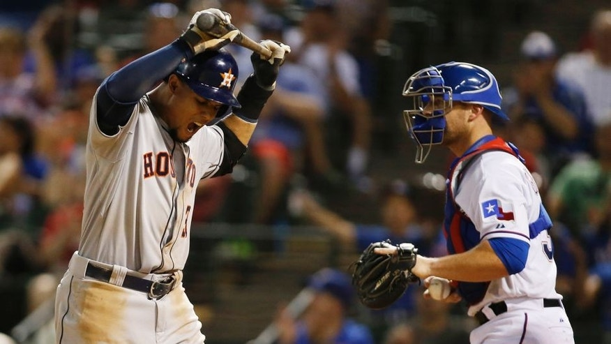 Aug 5, 2015; Arlington, TX, USA; Houston Astros center fielder Carlos Gomez (30) reacts to striking out in the ninth inning as Texas Rangers catcher Chris Gimenez (38) looks on at Globe Life Park in Arlington. Texas won 4-3. Mandatory Credit: Tim Heitman-USA TODAY Sports