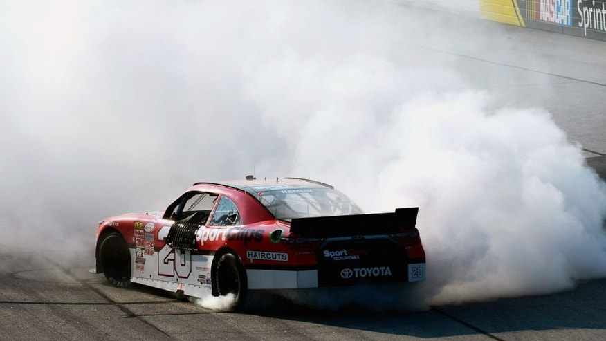 DARLINGTON, SC - SEPTEMBER 05: Denny Hamlin, driver of the #20 Sport Clips Toyota, celebrates with a burnout after winning the NASCAR XFINITY Series VFW Sport Clips Help A Hero 200 at Darlington Raceway on September 5, 2015 in Darlington, South Carolina. (Photo by Robert Laberge/NASCAR via Getty Images)