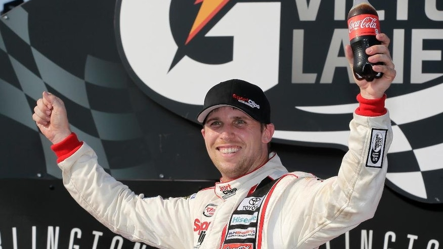 Denny Hamlin celebrates in victory lane after winning a NASCAR Xfinity auto race at Darlington Raceway in Darlington, S.C., Saturday, Sept. 5, 2015. (AP Photo/Terry Renna)