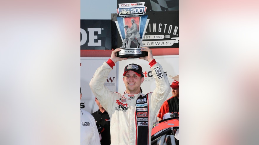 Denny Hamlin raises the trophy above his head after winning a NASCAR Xfinity auto race at Darlington Raceway in Darlington, S.C., Saturday, Sept. 5, 2015. (AP Photo/Terry Renna)
