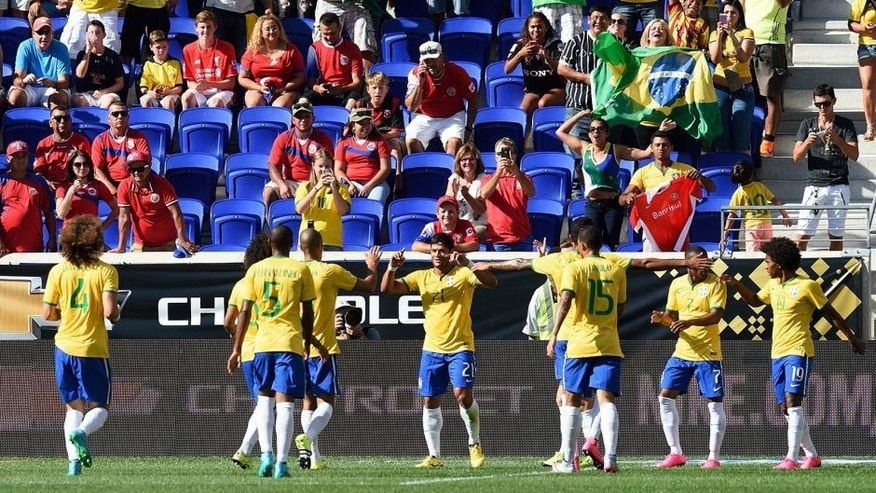 Brazil's Hulk (21) is congratulated by teammates after scoring a goal during the friendly match between Brazil and Costa Rica on September 5, 2015 at Red Bulls Arena in Harrison, New Jersey. AFP PHOTO/DON EMMERT (Photo credit should read DON EMMERT/AFP/Getty Images)