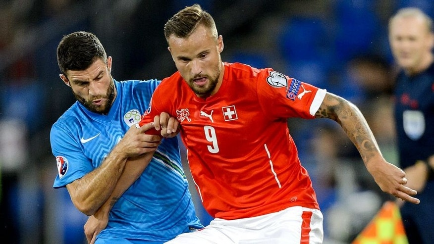 Slovenian defender Bojan Jokic (L) vies with Swiss forward Haris Seferovic during the Euro 2016 qualifying football match between Switzerland and Slovenia at the St. Jakob park stadium in Basel on September 5, 2015. AFP PHOTO / FABRICE COFFRINI (Photo credit should read FABRICE COFFRINI/AFP/Getty Images)