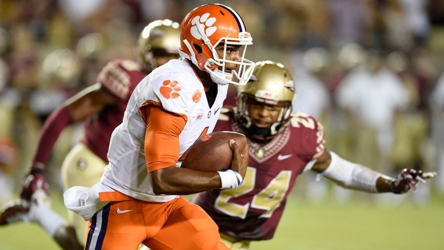 Sep 20, 2014; Tallahassee, FL, USA; Clemson Tigers quarterback Deshaun Watson (4) scrambles up the field against Florida State Seminoles linebacker Terrance Smith (24) during the first quarter at Doak Campbell Stadium. Mandatory Credit: John David Mercer-USA TODAY Sports
