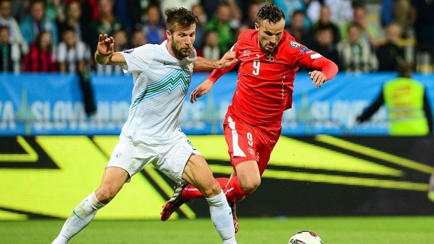 Slovenia's Bostjan Cesar (L) fights for the ball with Switzerland's Haris Seferovic on October 9, 2014 during a Euro 2016 qualifying match Slovenia vs. Switzerland in Maribor, Slovenia. AFP PHOTO / Jure Makovec (Photo credit should read Jure Makovec/AFP/Getty Images)