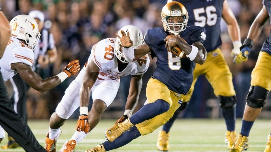 Sep 5, 2015; South Bend, IN, USA; Notre Dame Fighting Irish quarterback Malik Zaire (8) runs the ball as Texas Longhorns defensive end Naashon Hughes (40) pursues in the second quarter at Notre Dame Stadium. Mandatory Credit: Matt Cashore-USA TODAY Sports