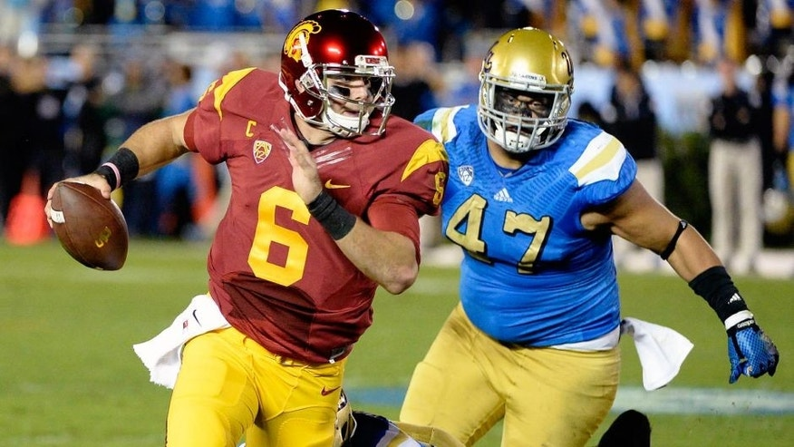 Nov 22, 2014; Pasadena, CA, USA; Southern California Trojans quarterback Cody Kessler (6) is pressured by UCLA Bruins defensive lineman Eddie Vanderdoes (47) and linebacker Deon Hollins (58) during the first half at the Rose Bowl. Mandatory Credit: Richard Mackson-USA TODAY Sports