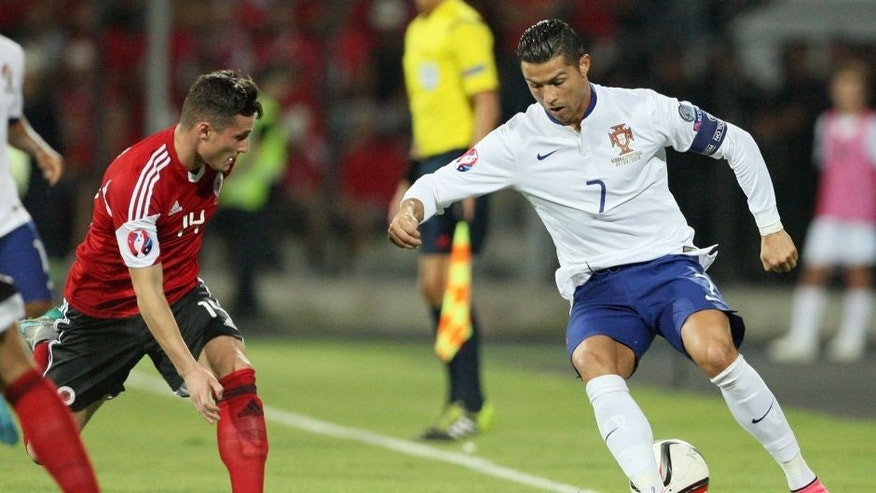 Albania's Taulant Xhaka vies with Portugal's Cristiano Ronaldo (R) during the Euro 2016 qualifying football match between Albania and Portugal at the Elbasan Arena in Elbasan on September 7, 2015. AFP PHOTO / GENT SHKULLAKU (Photo credit should read GENT SHKULLAKU/AFP/Getty Images)