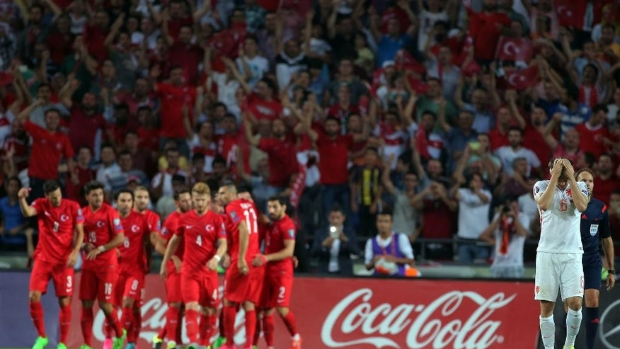 The Turkish team celebrate as Daley Blind of The Netherlands gestures, during their Euro 2016 Group A qualifying soccer match between Turkey and the Netherlands at the Buyuksehir Torku Arena Stadium in Konya, Turkey, Sunday, Sept. 6, 2015.(AP Photo)
