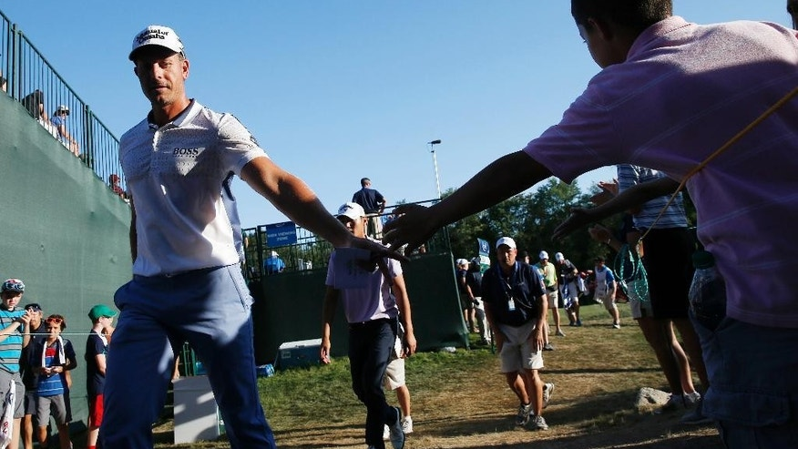 Henrik Stenson, of Sweden, reaches out to a young fan after finishing on the 18th hole during the third round of the Deutsche Bank Championship golf tournament in Norton, Mass., Sunday, Sept. 6, 2015. (AP Photo/Michael Dwyer)