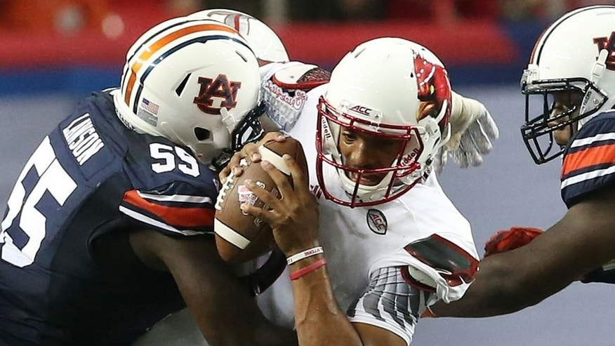 Auburn defensive lineman Carl Lawson (55) tackles Louisville quarterback Reggie Bonnafon (7) during the first half of an NCAA college football game, Saturday, Sept. 5, 2015, in Atlanta. (AP Photo/John Bazemore)