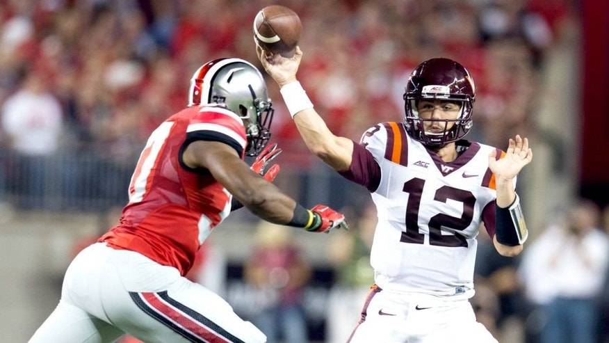 Sep 6, 2014; Columbus, OH, USA; Virginia Tech Hokies quarterback Michael Brewer (12) fires a pass under pressure from Ohio State Buckeyes linebacker Joshua Perry (37) at Ohio Stadium. Mandatory Credit: Greg Bartram-USA TODAY Sports