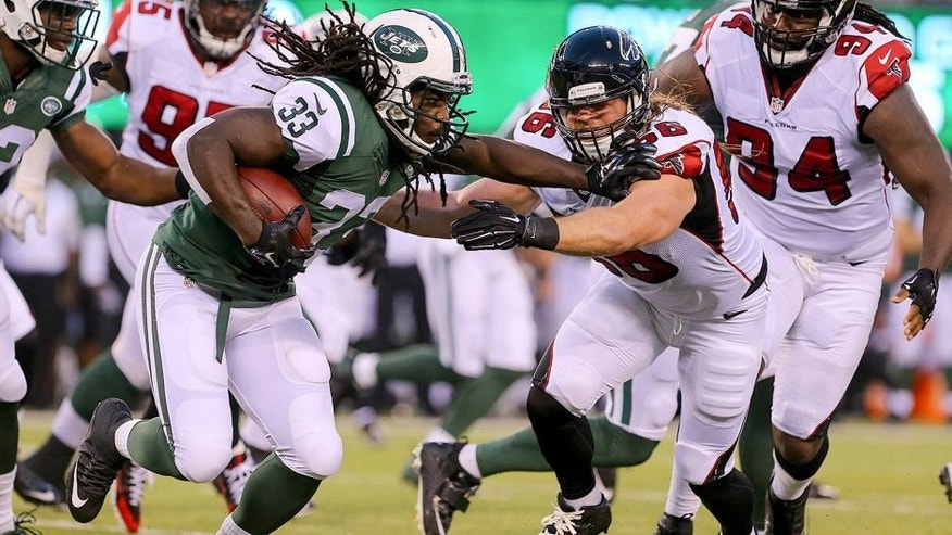 Aug 21, 2015; East Rutherford, NJ, USA; New York Jets running back Chris Ivory (33) runs with the ball while Atlanta Falcons linebacker Brooks Reed (56) attempts to tackle him during the first half at MetLife Stadium. Mandatory Credit: Ed Mulholland-USA TODAY Sports