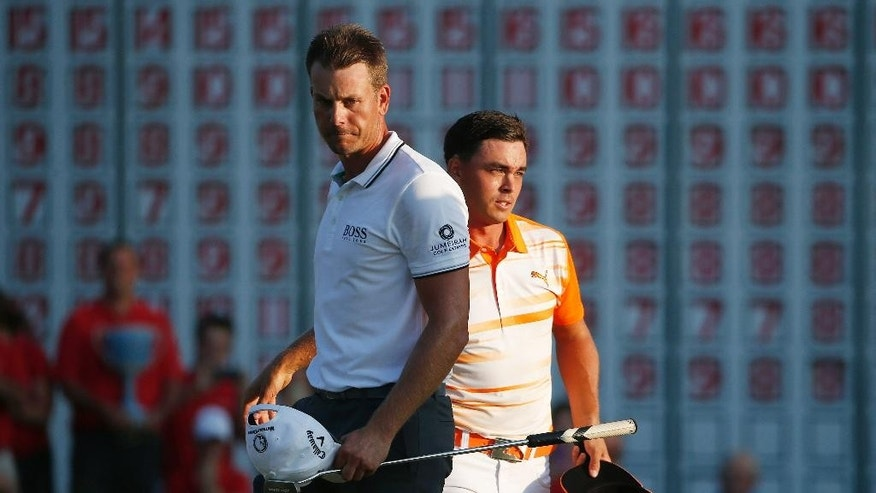 Rickie Fowler, right, and Henrik Stenson, of Sweden, separate after shaking hands after putting on the 18th hole during the final round of the Deutsche Bank Championship golf tournament in Norton, Mass., Monday, Sept. 7, 2015. Fowler won the tournament. (AP Photo/Michael Dwyer)