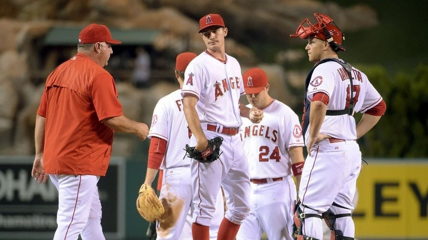 Sep 8, 2015; Anaheim, CA, UCA; Los Angeles Angels pitcher Andrew Hearney (center) reacts after being removed by manager Mike Scioscia (left) as catcher Chris Iannetta watches against the Los Angeles Dodgers at Angel Stadium of Anaheim. Mandatory Credit: Kirby Lee-USA TODAY Sports