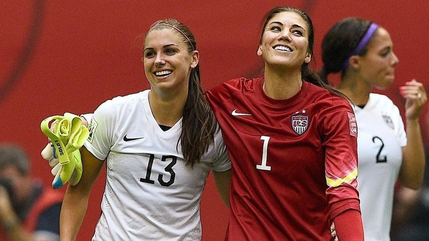 USA forward Alex Morgan (L) and goalkeeper Hope Solo celebrate after winning final football match between USA and Japan during their 2015 FIFA Women's World Cup at the BC Place Stadium in Vancouver on July 5, 2015. AFP PHOTO / FRANCK FIFE (Photo credit should read FRANCK FIFE/AFP/Getty Images)
