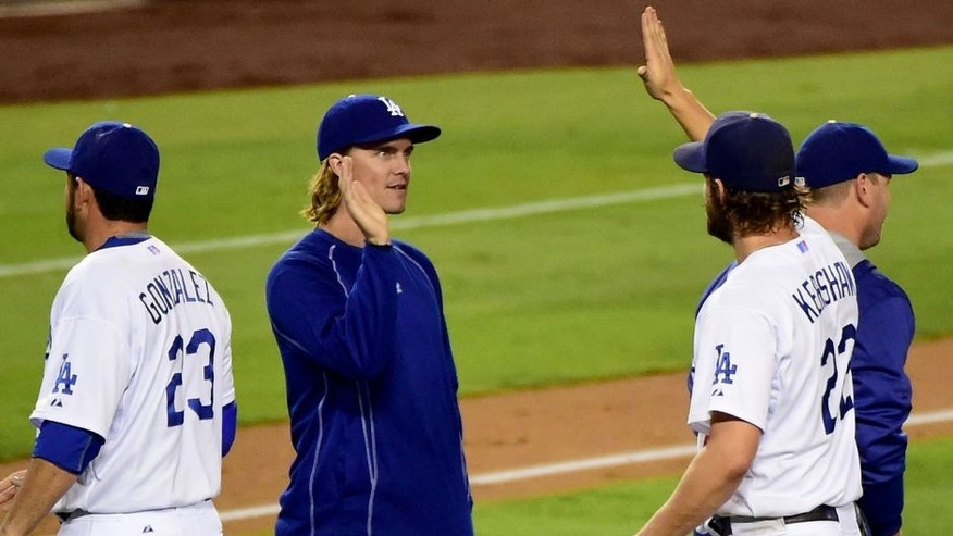 LOS ANGELES, CA - SEPTEMBER 02: Zack Greinke #21 of the Los Angeles Dodgers celebrates a 2-1 complete game win by Clayton Kershaw #22 over the San Francisco Giants at Dodger Stadium on September 2, 2015 in Los Angeles, California. (Photo by Harry How/Getty Images)