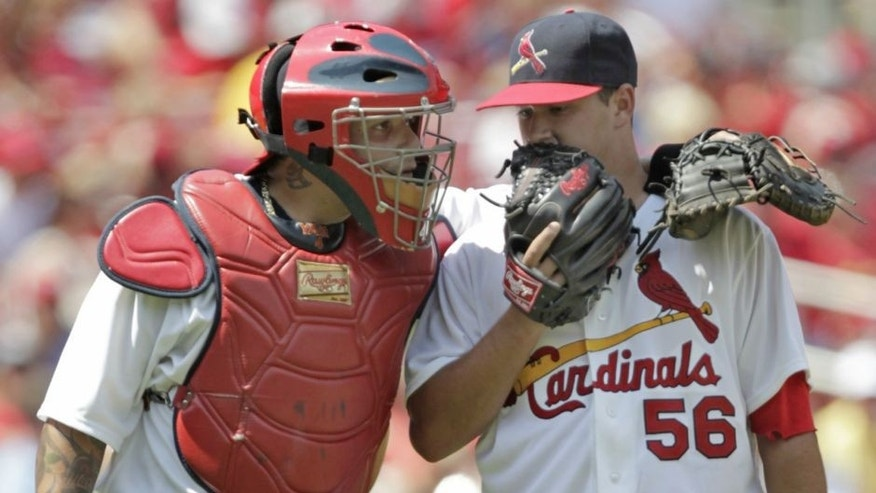 St. Louis Cardinals catcher Yadier Molina, left, talks with starting pitcher Marco Gonzales, right, in the fifth inning of a baseball game against the Miami Marlins, Sunday, July 6, 2014 in St. Louis. (AP Photo/Tom Gannam)
