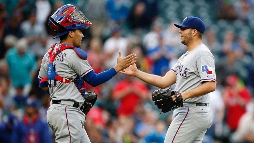 Sep 7, 2015; Seattle, WA, USA; Texas Rangers catcher Robinson Chirinos (61) and pitcher Shawn Tolleson (37) shake hands after beating the Seattle Mariners 3-0 at Safeco Field. Mandatory Credit: Jennifer Buchanan-USA TODAY Sports