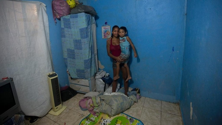 In this Aug. 10, 2015 photo, single mother Marcele de Oliveira Franca, 21, holds her 5-year-old son Kaike de Oliveira inside their one room apartment in the Rocinha slum of Rio de Janeiro, Brazil. When it rains, their basement apartment floods ankle-deep with a mixture of rainwater and sewage, and drinking water often comes out of the tap looking and smelling contaminated. Last year Kaike was hospitalized for two weeks with acute vomiting and explosive, bloody diarrhea that doctors attributed to a water-borne bacteria or virus. (AP Photo/Silvia Izquierdo)
