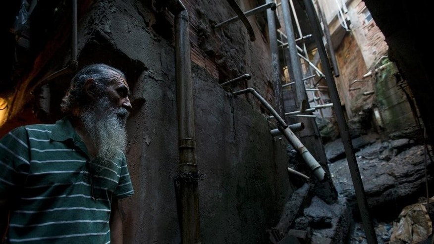 "In this Aug. 6, 2015 photo, Jose Martins, 68, stands near an open-air ditch in his Rocinha slum in Rio de Janeiro, Brazil. One public health expert calls the sewage system in Rio largely ""medieval,"" comparable with London or Paris in the 14th or 15th century. (AP Photo/Silvia Izquierdo)"