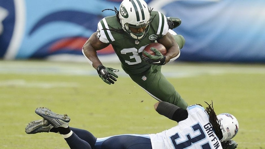 New York Jets running back Chris Ivory, top, is tripped up by Tennessee Titans safety Michael Griffin, bottom, in the first half of an NFL football game Sunday, Dec. 14, 2014, in Nashville, Tenn. (AP Photo/Mark Zaleski)