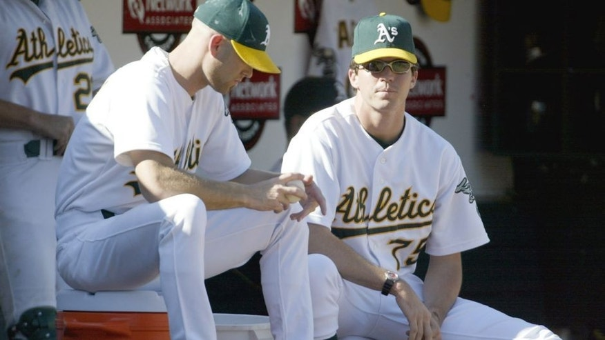 OAKLAND, CA - OCTOBER 6: Tim Hudson #15 and Barry Zito #75 of the Oakland Athletics watch from the dugout during game five of the American League Western Division Series against the Minnesota Twins at Network Associates Coliseum on October 6, 2002 in Oakland, California. The Twins defeated the A's 5-4. (Photo by Jed Jacobsohn/Getty Images)