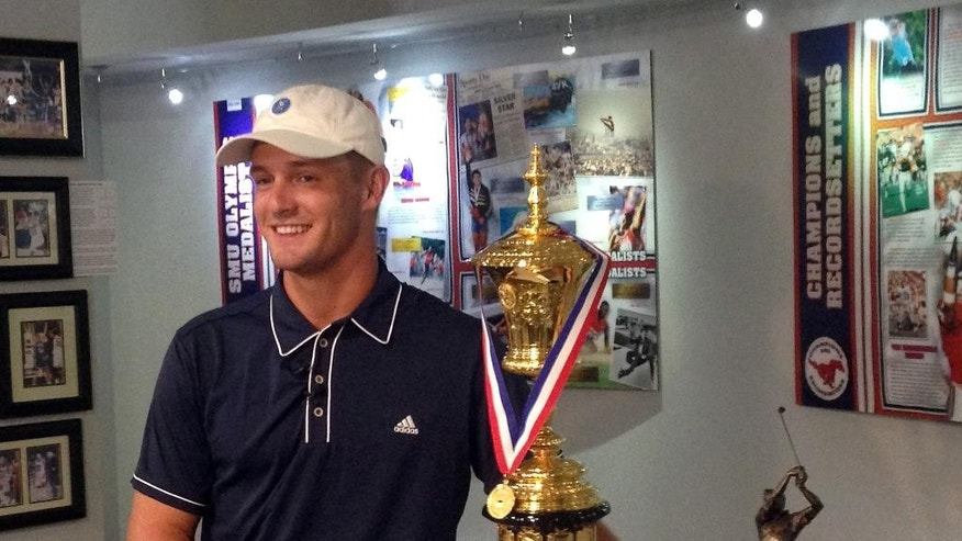 ADVANCE FOR WEEKEND EDITIONS, SEPT. 12-13 - Bryson DeChambeau is photographed with the U.S. Amateur Championship trophy at SMU's athletic Hall of Fame on Aug. 26, 2015 in Dallas. DeChambeau is a physics major with a unique mental approach to golf, and irons all the same length. The SMU senior, in the Walker Cup at St. Andrews this weekend, is only the fifth player ever to be the U.S. Amateur and NCAA individual champ in the same year. (AP Photo/ Stephen Hawkins)