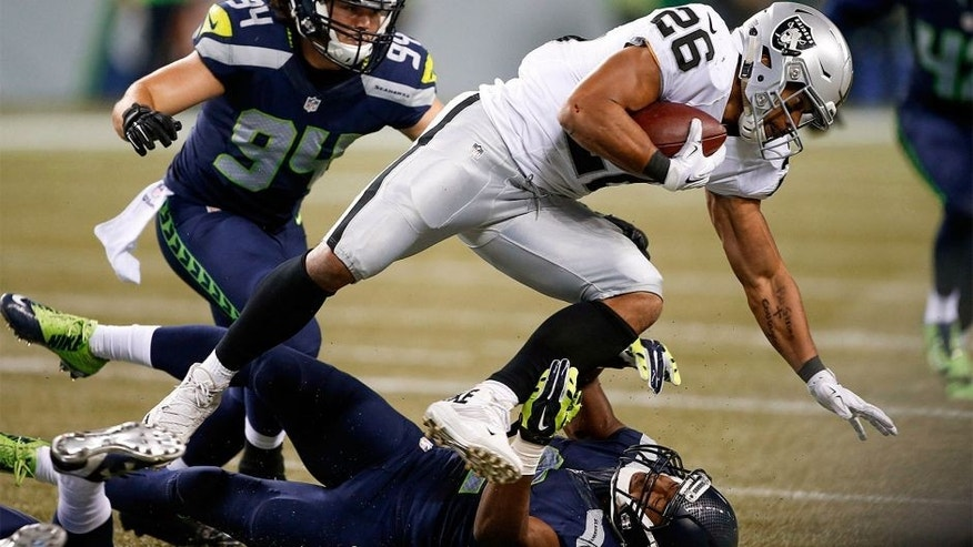 Sep 3, 2015; Seattle, WA, USA; Oakland Raiders running back Roy Helu, Jr. (26) is tackled by Seattle Seahawks safety Keenan Lambert (2) during the fourth quarter at CenturyLink Field. Mandatory Credit: Joe Nicholson-USA TODAY Sports