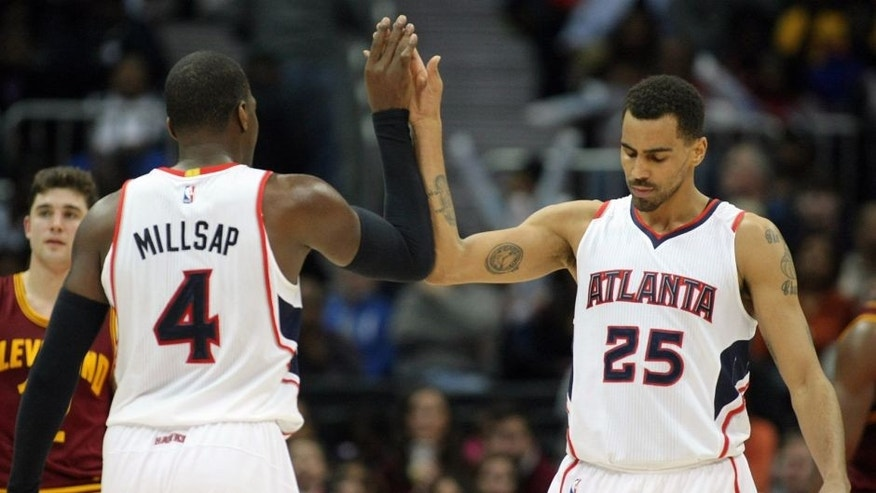 Dec 30, 2014; Atlanta, GA, USA; Atlanta Hawks forward Paul Millsap (4) celebrates with guard Thabo Sefolosha (25) against the Cleveland Cavaliers in the second quarter at Philips Arena. Mandatory Credit: Brett Davis-USA TODAY Sports