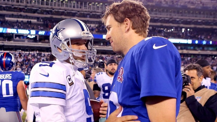 Nov 23, 2014; East Rutherford, NJ, USA; Dallas Cowboys quarterback Tony Romo (9) and New York Giants quarterback Eli Manning (10) after their game at MetLife Stadium. The Cowboys defeated the Giants 31-28. Mandatory Credit: Adam Hunger-USA TODAY Sports
