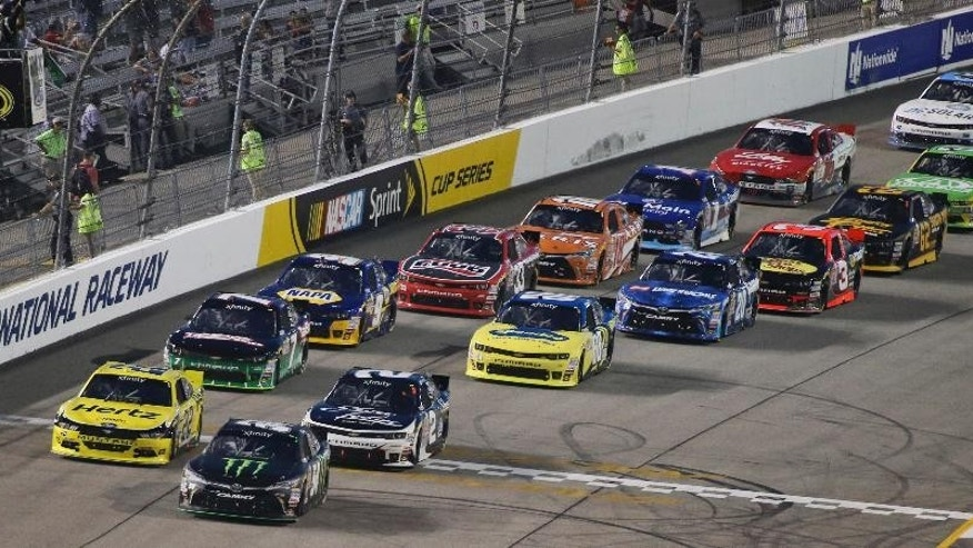 Kyle Busch (54) leads the field at the start of the NASCAR Xfinity auto race at Richmond International Raceway in Richmond, Va., Friday, Sept. 11, 2015. (AP Photo/Jason Hirschfeld)