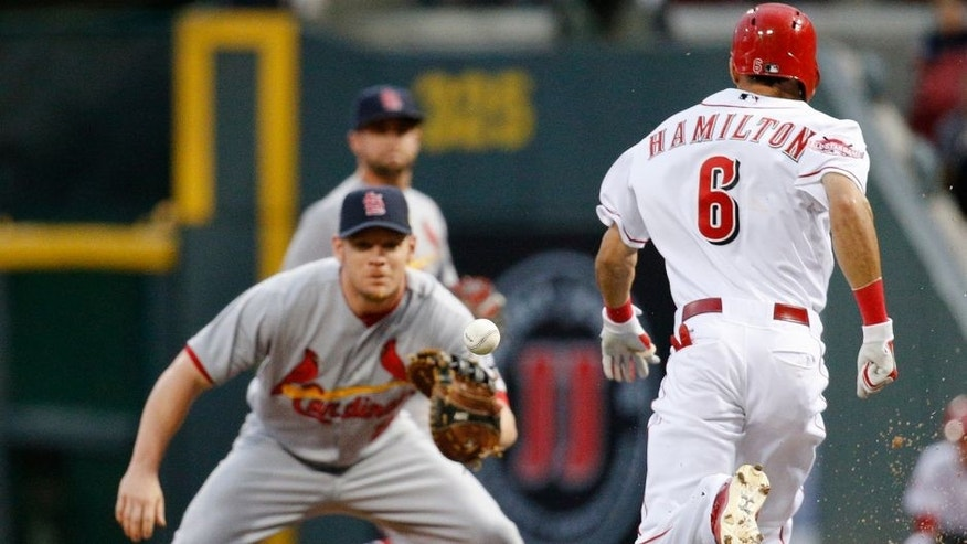Cincinnati Reds' Billy Hamilton (6) beats the throw to St. Louis Cardinals first baseman Brandon Moss, left, on a bunt during the first inning of a baseball game Friday, Sept. 11, 2015, in Cincinnati. (AP Photo/John Minchillo)