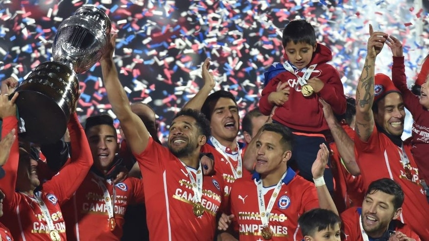Chilean players celebrate after winning the 2015 Copa America football championship final against Argentina, in Santiago, Chile, on July 4, 2015. Chile won 4-1 (0-0). AFP PHOTO / NELSON ALMEIDA (Photo credit should read NELSON ALMEIDA/AFP/Getty Images)