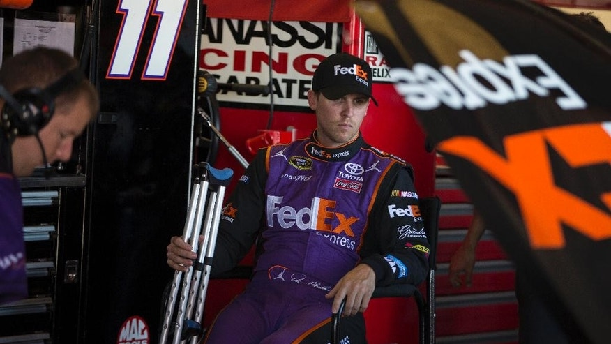 Denny Hamlin sits in his garage during practice for the NASCAR Sprint Cup auto race at Richmond International Raceway in Richmond, Va., Friday, Sept. 11, 2015. Hamlin, who tore an ACL, will be racing despite his injury. (AP Photo/Chet Strange)