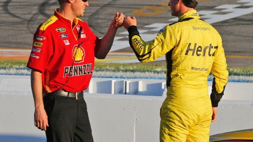 Joey Logano, right, fist-bumps a crew member after qualifying on the pole for Saturday's NASCAR Sprint Cup auto race at Richmond International Raceway in Richmond, Va., Friday, Sept. 11, 2015. (AP Photo/Steve Helber)