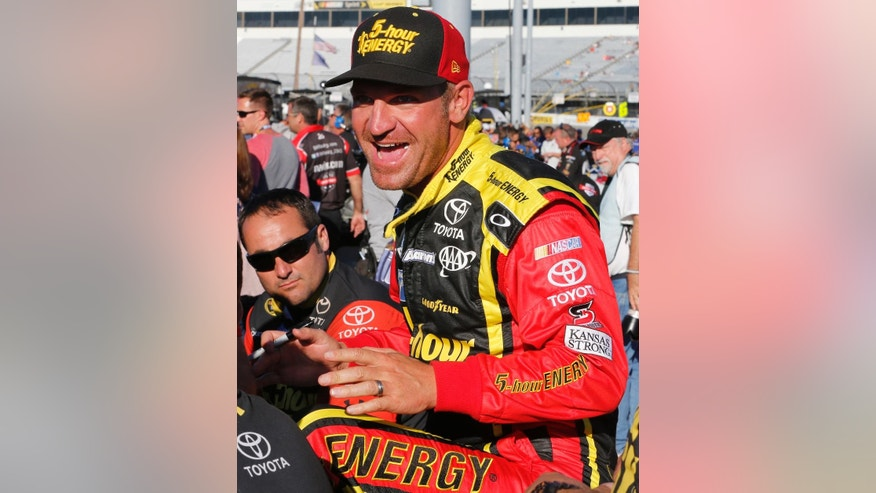 Clint Bowyer jokes with his pit crew prior to qualifying for Saturday's NASCAR Sprint Cup race at Richmond International Raceway in Richmond, Va., Friday, Sept. 11, 2015. (AP Photo/Steve Helber)