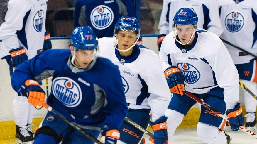 FILE - In this July 1, 2015, file photo, Connor McDavid, right, skates during the Edmonton Oilers' orientation camp in Edmonton, Alberta.  All eyes are on the 18-year-old forward, a can't miss player and the No. 1 pick. He is also the No. 1 reason why the Oilers seem suddenly poised for a revival after missing the playoffs for nine consecutive seasons, the NHL's longest active drought.  (John Ulan/The Canadian Press via AP, File)