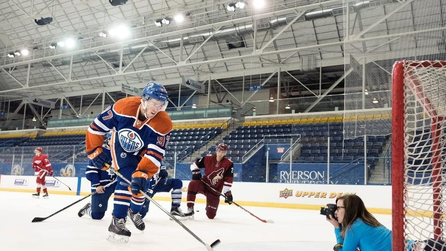 FILE - In this Tuesday, Sept. 1, 2015, file photo, Edmonton Oilers' Connor McDavid shoots a puck over a photographer during the National Hockey League Players Association (NHLPA) Rookie Showcase in Toronto.  All eyes are on the 18-year-old forward, a can't miss player and the No. 1 pick. He is also the No. 1 reason why the Oilers seem suddenly poised for a revival after missing the playoffs for nine consecutive seasons, the NHL's longest active drought.  (Darren Calabrese/The Canadian Press via AP, File)