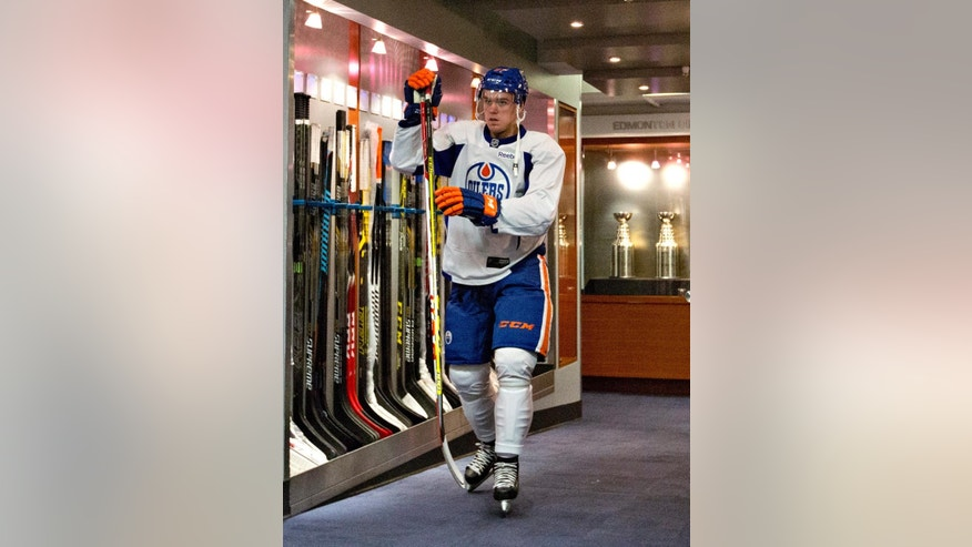 FILE - In this July 2, 2015, file photo, Edmonton Oilers first-round pick Connor McDavid walks out to the ice for the NHL hockey team's orientation camp in Edmonton, Alberta.  All eyes are on the 18-year-old forward, a can't miss player and the No. 1 pick. He is also the No. 1 reason why the Oilers seem suddenly poised for a revival after missing the playoffs for nine consecutive seasons, the NHL's longest active drought.  (Jason Franson/The Canadian Press via AP, File)