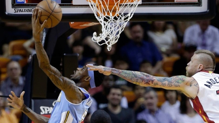 Denver Nuggets' Will Barton, left, attempts a shot against Miami Heat's Chris Andersen, right during the first half of an NBA basketball game, Friday, March 20, 2015, in Miami. (AP Photo/Lynne Sladky)