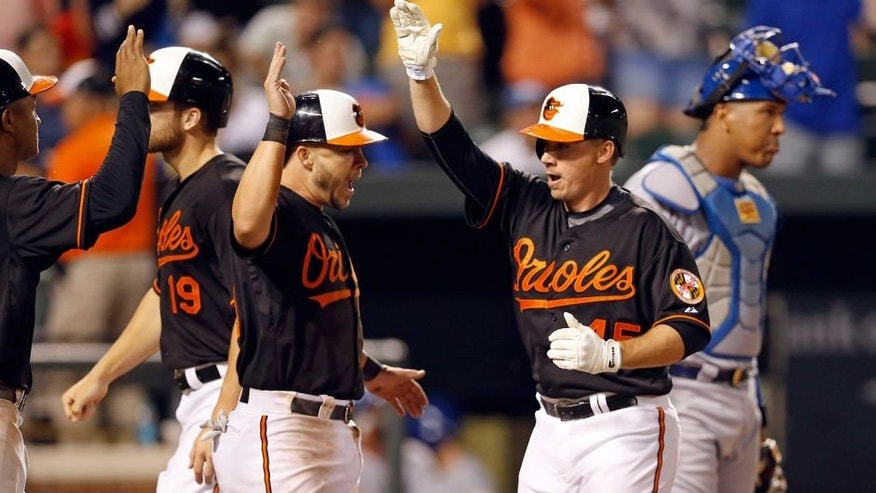 Baltimore Orioles' Steve Clevenger, second from right, celebrates his grand slam with teammates Jonathan Schoop, left, Chris Davis (19) and Steve Pearce, next to Kansas City Royals catcher Salvador Perez during the eighth inning of a baseball game, Friday, Sept. 11, 2015, in Baltimore. The Orioles won 14-8. (AP Photo/Patrick Semansky)