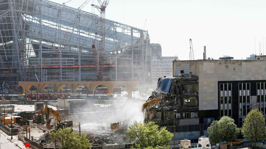 <p>The new U.S. Bank Stadium, home of the Minnesota Vikings NFL football team which opens in 2016, looms in the background as demolition of the Star Tribune building, right, continues Thursday, Sept. 10, 2015, to make room for a park adjacent to the stadium in Minneapolis. The city council is expected to vote Friday on whether to approve the design and fundraising arrangement for the park. (AP Photo/Jim Mone)</p>