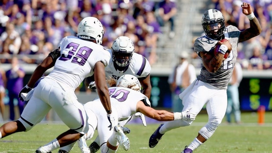FORT WORTH, TX - SEPTEMBER 12: Trevone Boykin #2 of the TCU Horned Frogs carries the ball against Chance Barney #39 of the Stephen F. Austin Lumberjacks and Justin Owens #30 of the Stephen F. Austin Lumberjacks in the second quarter at Amon G. Carter Stadium on September 12, 2015 in Fort Worth, Texas. (Photo by Tom Pennington/Getty Images)