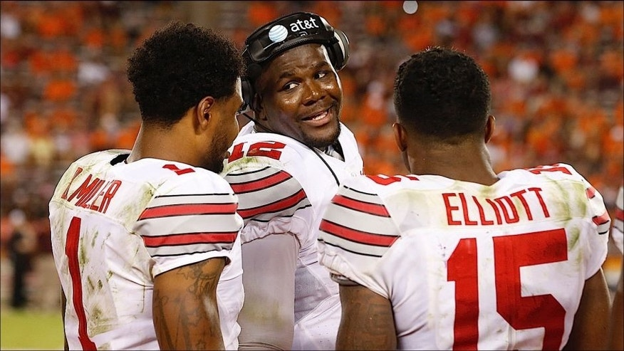 <p>Ohio State quarterback Cardale Jones, center, talks with teammates Ezekiel Elliott (15) and Braxton Miller, left, during the second half of an NCAA college football game in Blacksburg, Va., Monday, Sept. 7, 2015. Ohio State won 42-24. (AP Photo/Steve Helber)</p>