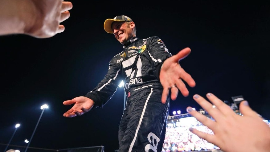 Jamie McMurray reaches for fans as he is introduced as a competitor of the Chase for the Sprint Cup champonship, after the NASCAR auto race at Richmond International Raceway in Richmond, Va., Saturday, Sept. 12, 2015. (AP Photo/Chet Strange)