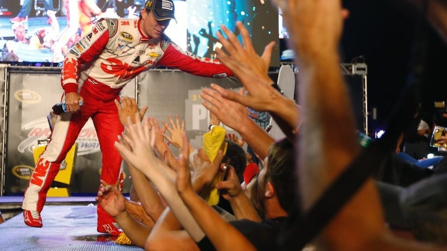 Jeff Gordon reaches for fans as he is introduced as a member of the Chase for the Sprint Cup championship after the NASCAR auto race at Richmond International Raceway in Richmond, Va., Saturday, Sept. 12, 2015. (AP Photo/Chet Strange)